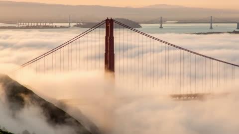 san francisco golden gate bridge låg dimma morgon ljus - hängbro bildbanksvideor och videomaterial från bakom kulisserna