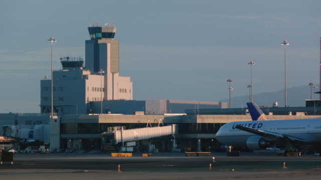 san francisco international airport terminal and tower exterior with united airlines jet crossing foreground late afternoon - san francisco international airport stock videos & royalty-free footage