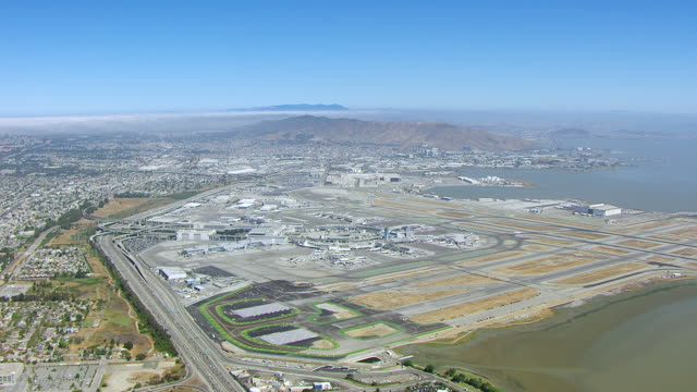 ws aerial pov san francisco international airport with large landscape and bay of water, crowded city seen in background / san francisco, california, united states - san francisco international airport stock videos & royalty-free footage