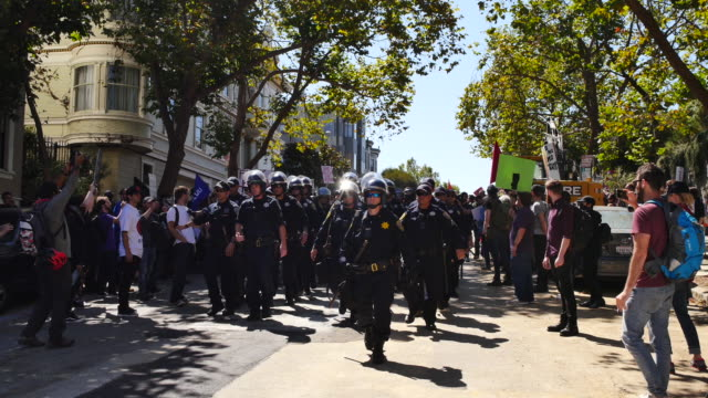 san francisco police walk through protesters near alamo square in san francisco california where protesters gathered after members of patriot prayer... - anti fascism stock videos & royalty-free footage
