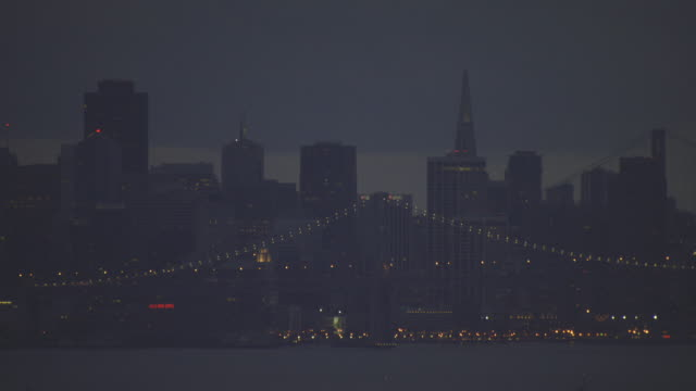 ds san francisco skyline illuminated behind the oakland bay bridge / california, united states - san francisco bay stock videos and b-roll footage