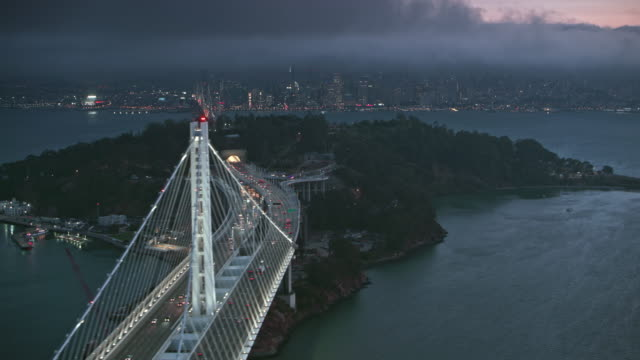 AERIAL San Francisco-Oakland Bay Bridge and the Yerba Buena Island at dusk overlooking the city of San Francisco