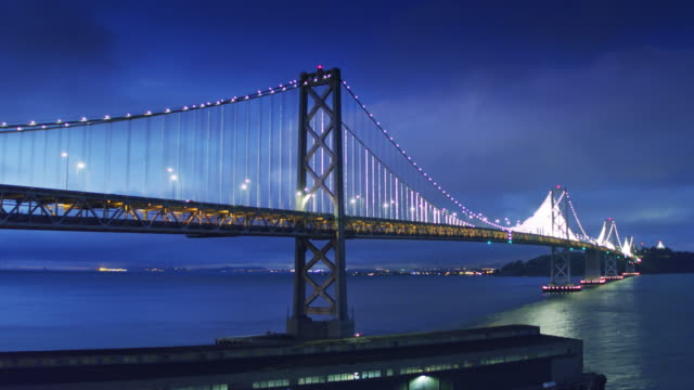 san francisco-oakland bay bridge lit up at night - drone shot - san francisco oakland bay bridge stock videos and b-roll footage