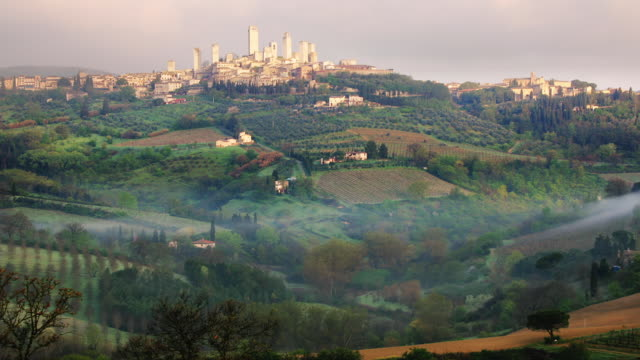 vidéos et rushes de t/l ws san gimignano and surrounding countryside with early morning mist / italy - toscane