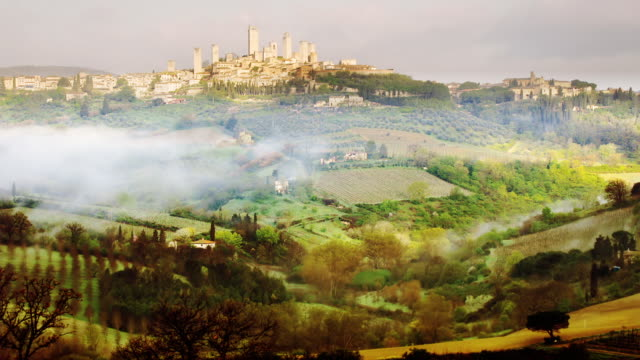 T/L WS San Gimignano and surrounding countryside with early morning mist / Italy
