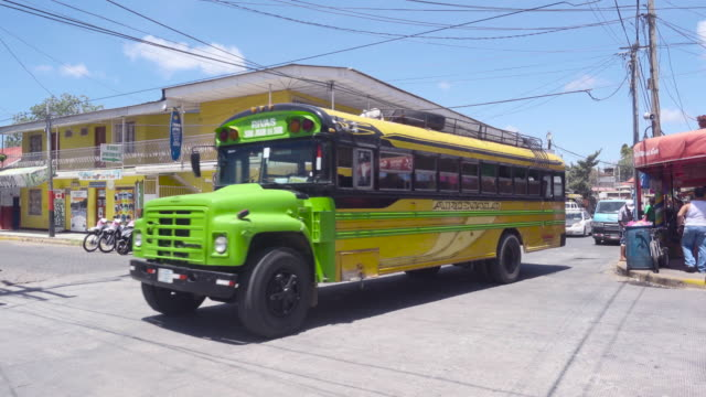 san juan del sur nicaragua. colorful green bus leaves from mercado market avenue to rivas terminal. tourists, travelers and locals walking on the street and going by bike. - nicaragua stock videos and b-roll footage