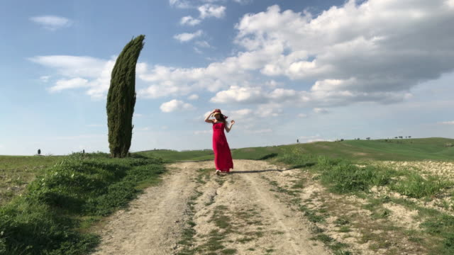 vidéos et rushes de san quirico d'orcia, orcia valley, siena, tuscany. girl in red dress walking on a country road - robe rouge
