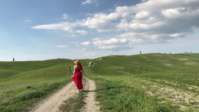San Quirico d'orcia, Orcia Valley, Siena, Tuscany. Girl in red dress walking on a country road