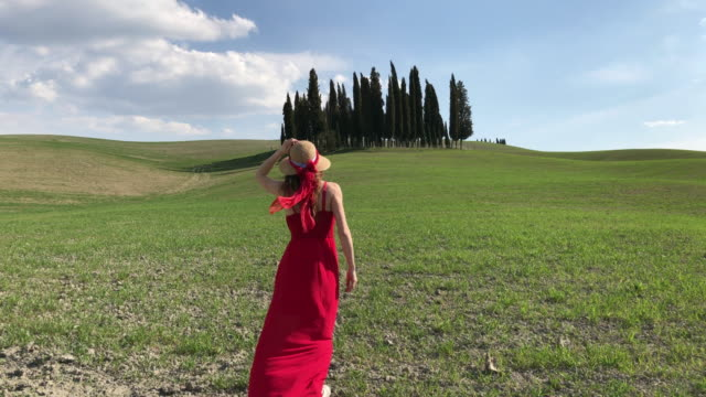 San quirico d'Orcia, Orcia Valley, Tuscany. Girl in red dress is walking near the cypresses of Val d'Orcia