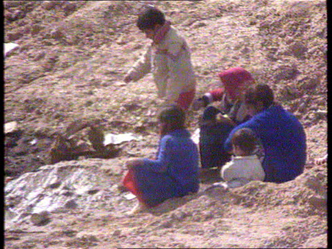 sanctions iraq tgv tented refugee camp tms children sitting in group pull out tms two women next tent tgv camp - 制裁点の映像素材/bロール