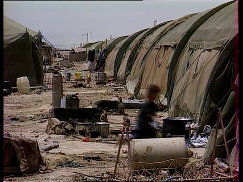 sanctions iraq gv refugee tents with people to and fro gv ditto int / tent tms family sitting tms two people lying on ground sheet tcms ditto two men... - 制裁点の映像素材/bロール