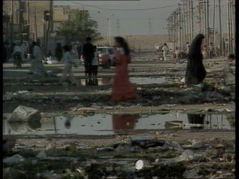 robin cook statement/response lib iraq baghdad people along thru sewage and water in street tms small boy along thru sewage water in street - ロビン クック点の映像素材/bロール