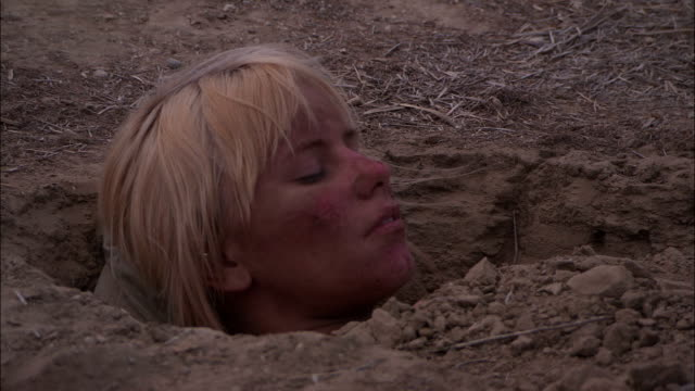 vídeos de stock e filmes b-roll de sand and dirt cover the body of an unconscious woman. - enterrado