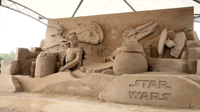 vídeos de stock, filmes e b-roll de sand artist works on the sand sculpture ahead of the promotional exhibition for the movie star wars the sculpture created by the sand sculptor as a... - série de filmes star wars