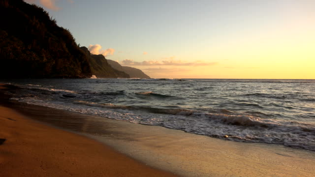 sand beach under red sunset on kauai island - butte rocky outcrop stock videos & royalty-free footage