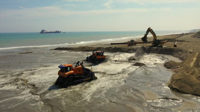 vidéos et rushes de sand being pumped onto norfolk beach at bacton and diggers moving it in sandscaping project to save eroding area of coastline - érodé