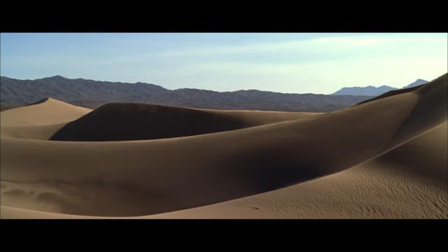 vidéos et rushes de aerial sand blowing from the peaks of sand dunes - format vignette