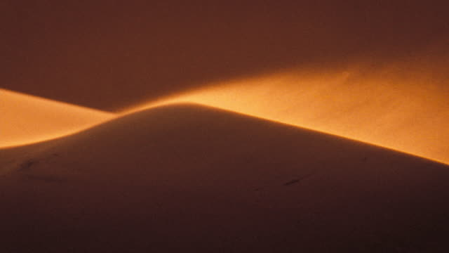 Sand blows across dunes in the Kalahari Desert. Available in HD.