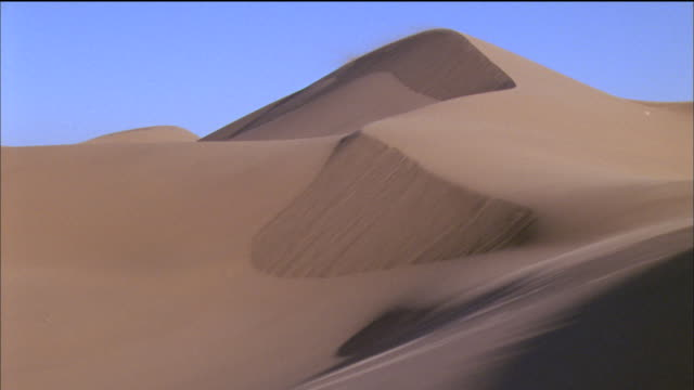 sand blows over dunes available in hd. - sand dune stock videos & royalty-free footage