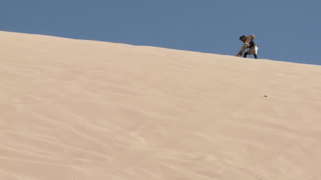 slo mo sand dune with sand-boarder on ridge preparing board / san pedro de atacama, chile - solo un uomo di età media video stock e b–roll
