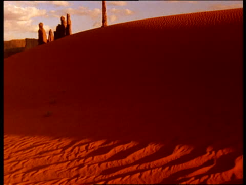 sand dunes and rock formations appear red at golden hour. - golden hour stock videos & royalty-free footage