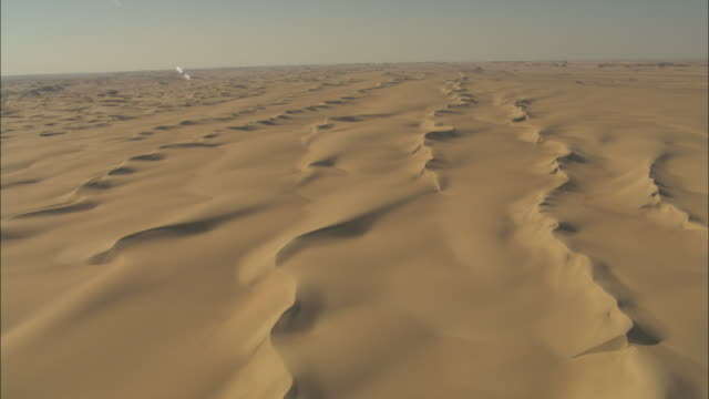 ,  - Sand dunes appear as ripples on the desert landscape / Egypt