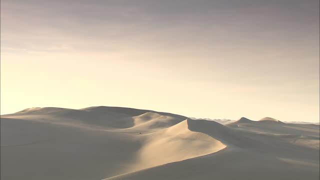 vídeos y material grabado en eventos de stock de sand dunes cover a desolate desert area. - duna de arena