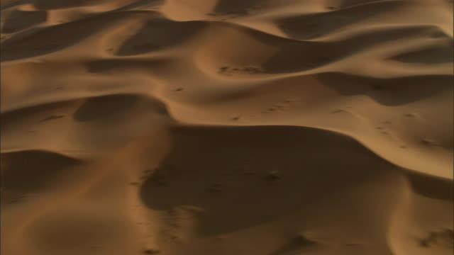 sand dunes ripple across gilf kebir, egypt. - sanddüne stock-videos und b-roll-filmmaterial