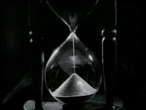 Sand falls through an hourglass