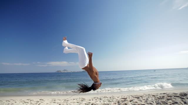 Sand flies as Brazilian martial artist flips backwards across Ipanema Beach in slow motion