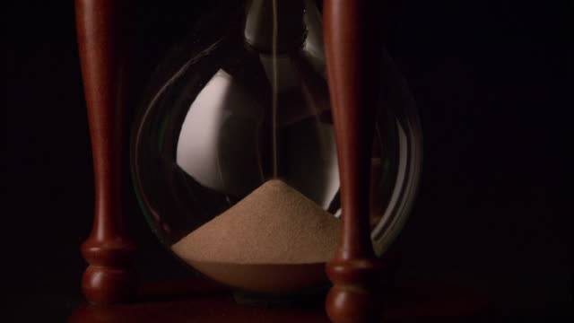 sand flows through an hourglass. - hourglass stock videos & royalty-free footage