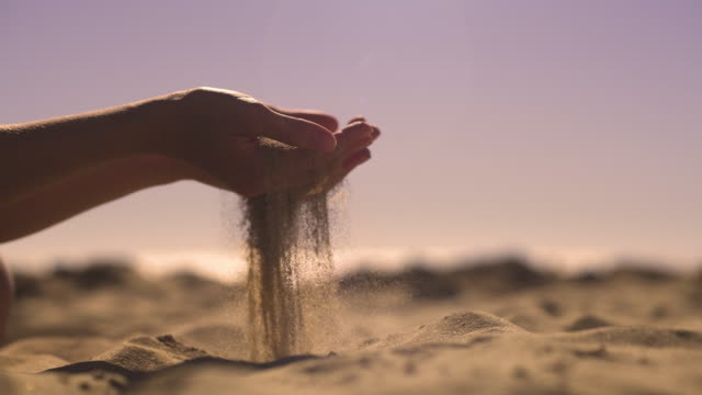 Sand in hands at sunset