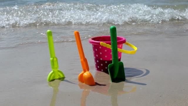sand pail and shovel in water on the beach