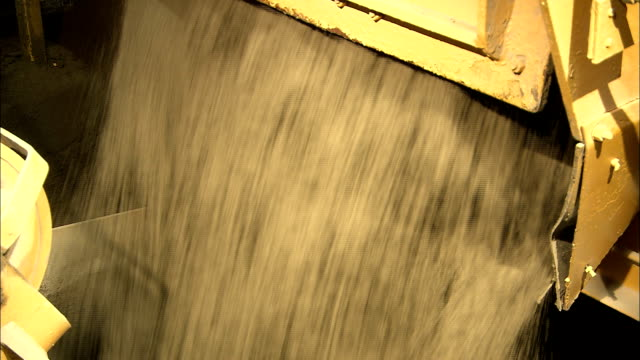 sand pours down a chute in a cement factory. - cement mixer stock videos & royalty-free footage