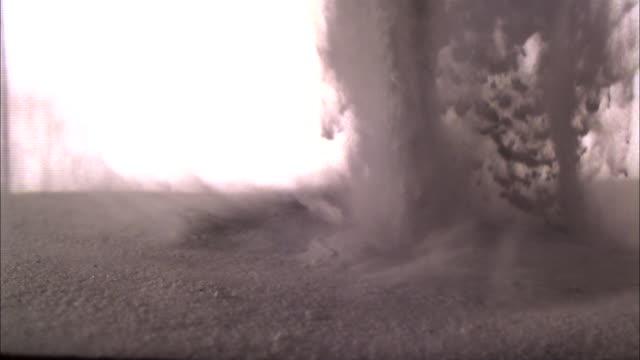 sand pours down onto a surface of more sand in slow motion. - kornig bildbanksvideor och videomaterial från bakom kulisserna