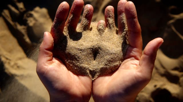 sand running through fingers. - sandig stock-videos und b-roll-filmmaterial
