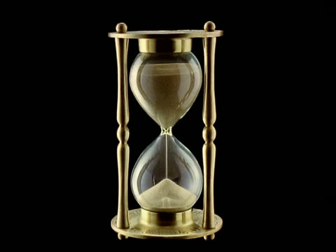 t/l - sand running through hourglass egg timer, black background - hourglass stock videos & royalty-free footage