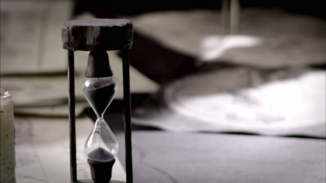 sand sifts through an hourglass as nostradamus measures parchment with a compass. - hourglass stock videos & royalty-free footage