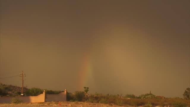 vídeos y material grabado en eventos de stock de sand storm with rainbow approaching town, yellow sand hangs in air under dark storm clouds, arizona, usa. - vendaval de polvo