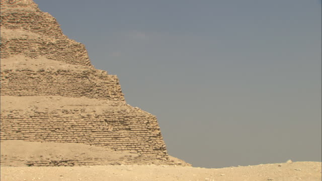 sand surrounds the ancient saqqara pyramid in egypt. - saqqara stock videos and b-roll footage