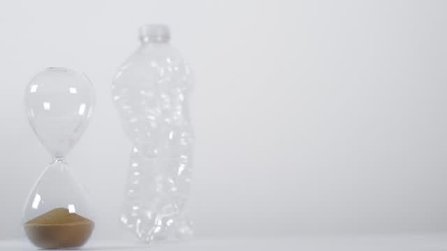 vídeos de stock e filmes b-roll de sand timer runs out next to crushed plastic bottle - utilização única