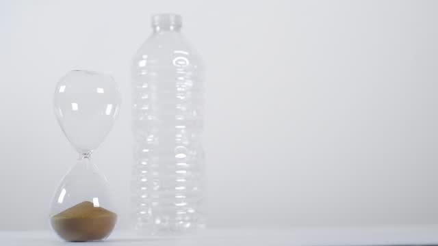 vídeos de stock e filmes b-roll de sand timer runs out next to plastic bottle - utilização única