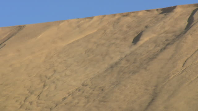 sand unpacks and slides down a dune. available in hd. - sliding stock videos & royalty-free footage