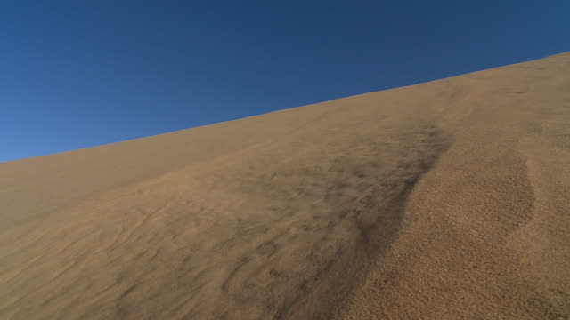 sand unpacks and slides down a dune. available in hd. - sand dune stock videos & royalty-free footage