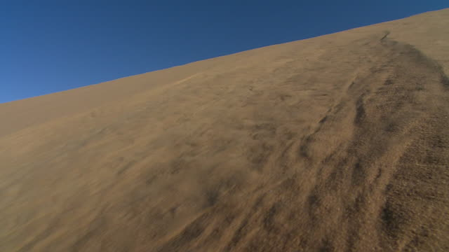 vídeos y material grabado en eventos de stock de sand unpacks and slides down a dune. available in hd. - deslizar