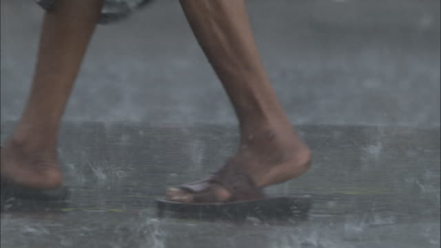 sandalled feet of man in rain as traffic passes by, kolkata, india available in hd. - kolkata stock videos & royalty-free footage