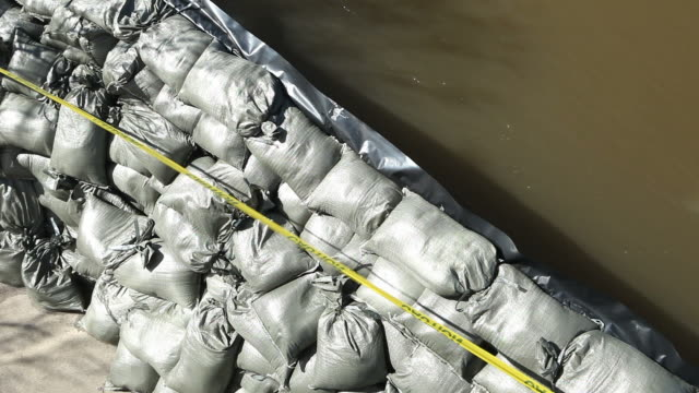 sandbag wall separates water from dry land - sandbag stock videos and b-roll footage