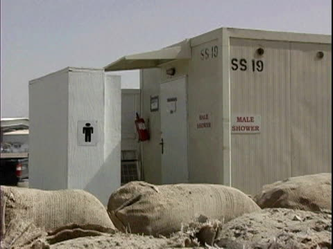 sandbags surrounding male shower facility at camp victory / baghdad iraq / audio - campo militare video stock e b–roll