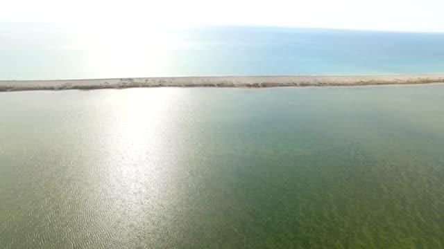 aerial: sandbank between blue sea and salt lakes - shallow stock videos & royalty-free footage