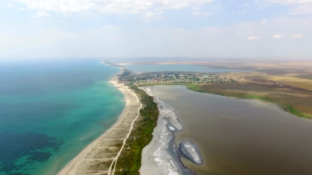 aerial: sandbank between blue sea and salt lakes - backwater stock videos & royalty-free footage